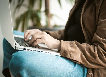Freelancer woman works with laptop computer using internet while sitting on windowsill. Close up shot. Lifestyle concept.