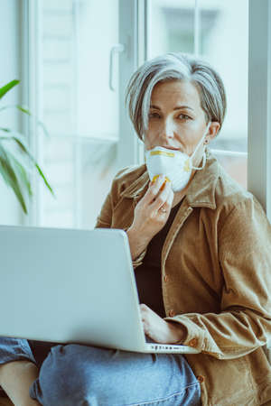 Sad woman took off her face mask looking at camera. Female freelancer working with laptop at home during Coronavirus pandemic. Stock fotó