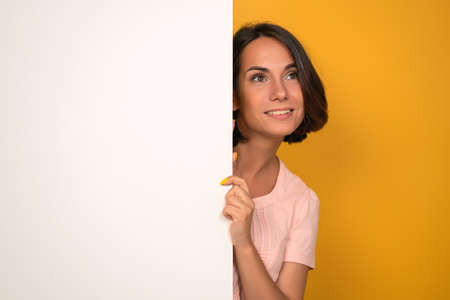 Young woman looks up holding white empty blank with copy space on it. Isolated on yellow background. Studio shot.