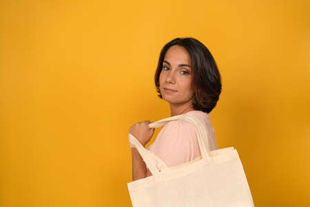 Charming woman holds eco bag on her shoulder looking at camera. Shopping concept. Cut out on yellow background. Copy space.