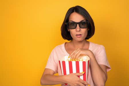 Surprised young woman in dark eyeglasses holding box of popcorn. Cinema concept. Isolated on yellow background. Copy space at left.