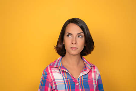 Thinking young woman makes serious decision. Pretty brunette looks up at copy space on left. Isolated on yellow background.