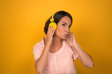 Young woman listens to music with yellow headphones. Caucasian brunette dancing and singing on a yellow background.