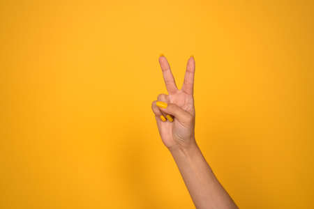V sign. Female hand shows two fingers or peace gesture. Cut out on yellow background. Copy space.