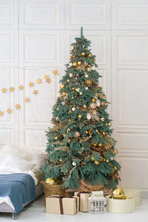 Decorated Christmas tree with gifts underneath. Festive bedroom interior with white walls.