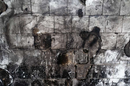 Monochrome spotted tiled wall after fire. Abstract grunge background. High quality photo. 免版税图像