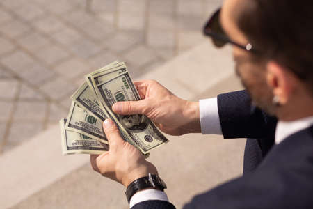 Close up of successful american businessman considering wad of 100 dollar banknotes while sitting on sidewalk. Rear view.