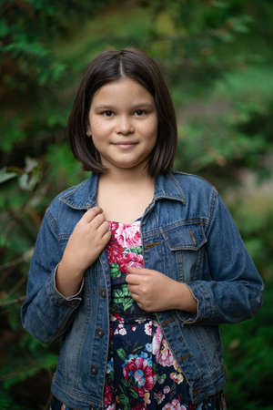 Cute little girl wearing plaid dress and denim jacket posing against backdrop of green nature.