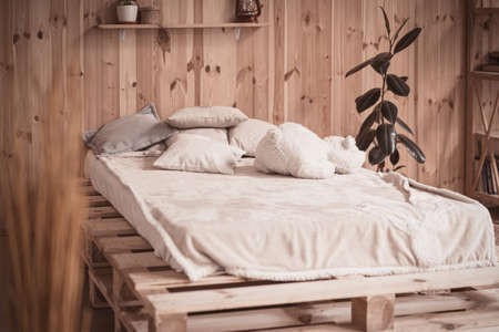 Cozy bed with pillows and bear toy in wooden home interior. 免版税图像