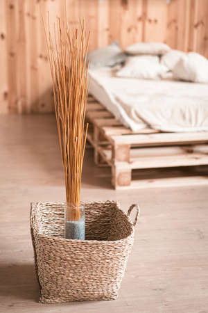 Natural home decor in wooden interior of bedroom. Bouquet of dried sticks in vase and wicker basket at floor.