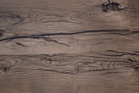 Nature material. Close up shot of wooden board with dark cracks. Abstract background or texture.