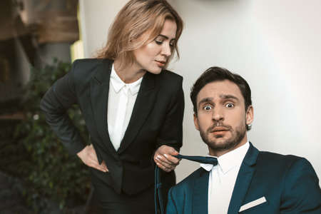 Pretty businesswoman seduces her male boss or collegue. Caucasian female holding tie of businessman. Sexual harassment concept. 免版税图像