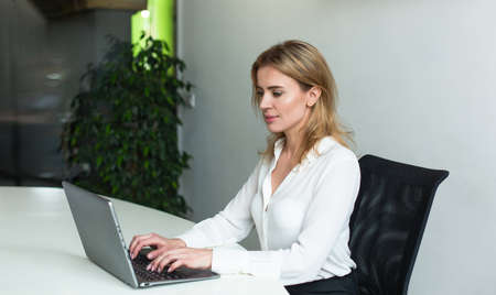 Pretty businesswoman working with computer in office. Young Caucasian lady typing at laptop.