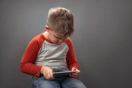 Preschool boy using mobile phone. Child in studio holds big smartphone speaking on it with friends online. Technology concept.