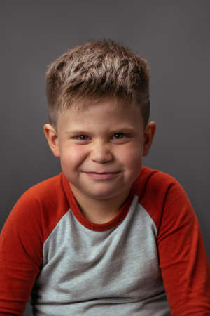Preschool boy smiling with smirk at camera. Portrait of funny child on gray background. Emotions concept.