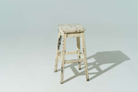 Tall retro stool or tabouret with peeling white paint on white background. Empty place.