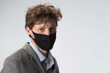 Modern serious man in black face mask on white background. Head and shoulders portrait.