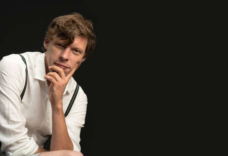 Thoughtful man in white shirt looks at camera against black background. Empty space for text.