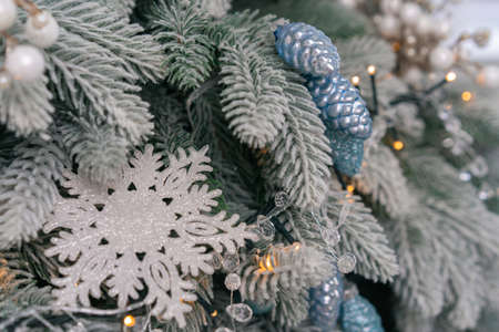 Decorated branch of Christmas tree with garlands and cones. Close up shot. Background or template for Holiday card with copy space at left side.