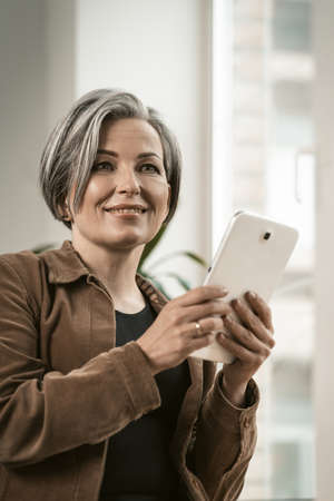 Pretty woman of retired age smiles communicating online on digital tablet while standing near window. Technology concept.