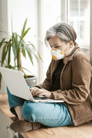 Greying businesswoman works laptop from home. Aged woman wearing protective mask uses mobile internet on computer sitting at windowsill. Qurarantine concept.