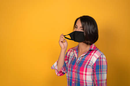 Cute young woman with face protective mask during quarantine. Isolated on yellow background. Virus outbreak concept. 免版税图像