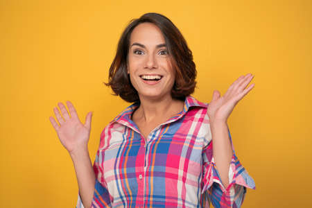 Enthusiastic woman raising up her hands. Smiling young brunette in casual cut out on yellow background.