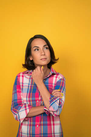 Thoughtful woman looks up at copy space on right side while touhing her chin with hand. Isolated on yellow background in studio.