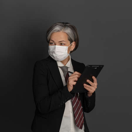 Masked Caucasian businesswoman writes with pen in blank while looking at side. Quarantine concept.