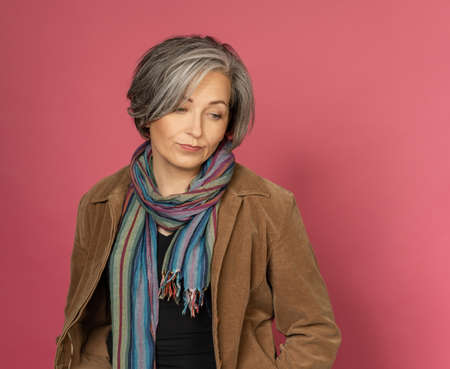 Beautiful woman slightly smiles making duck lips and looking at side. Sexy grey haired model posing in studio. Cut out on pink background. 免版税图像
