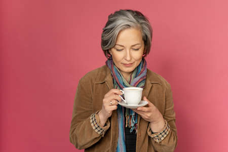 Charming elegant woman drinks coffee or tea holding white cup looking on it. Isolated on pink background with copy space. Studio shot. 免版税图像