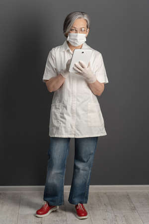 Female doctor wearing white coat and jeans full length. Mature woman in protective mask working with digital device.