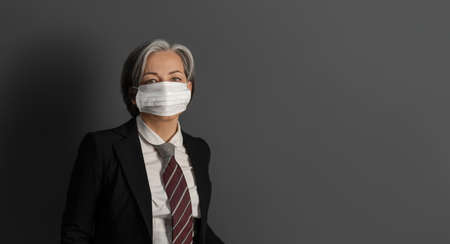 Serious gray haired businesswoman wearing protective mask and formalvear isolated on gray background. Copy space at right.