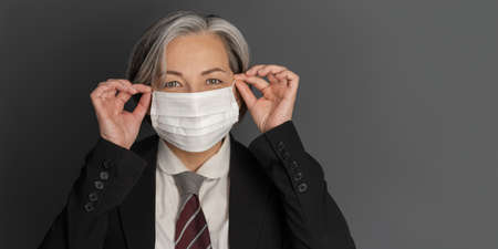 Mature businesswoman straightens protective mask on her face. Positive woman smiles at camera. Cut out on gray background with copy space on right.