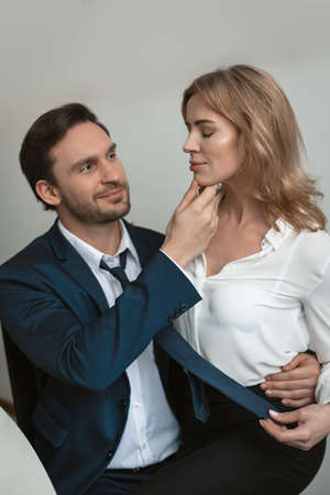Couple of business man and woman wearing formalwear flirting while hugging and touching each other.