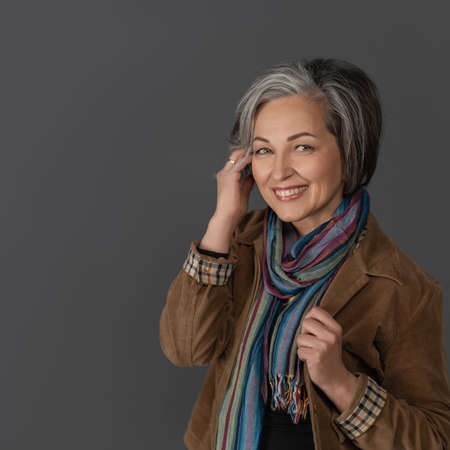 Creative mature woman in casual touching her graying short hair. Studio portrait on gray background. Copy space at left. Hairstyle concept. 免版税图像