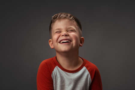 Portrait of a child. Funny little caucasian boy laughing in studio. Isolated on grey background. High quality photo