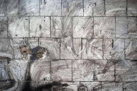 Abstract grunge background. Dirty tiles on the wall with blurry traces of soot and dust. Gray charred wall after fire. Фото со стока