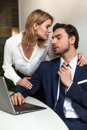 Passionate couple flirts in the office. Businessman looks on woman touching him from back while standing near workplace. Seducing concept.