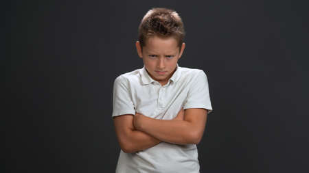 Angry schoolboy crossed hand frowning face. Isolated on gray background. Copy space.