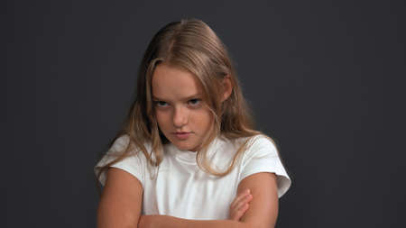 Disgruntled girl crossed her arms looking to side. Teen model expresses sad emotion. Problem concept. Close up shot. Isolated on gray background. Copy space. Stok Fotoğraf