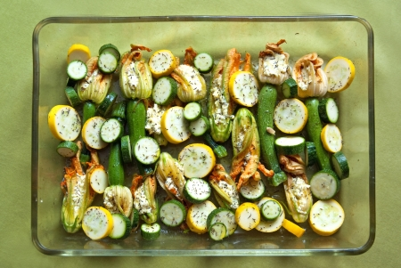 resistant: Green and yellow zucchini with stuffed flowers prepared to bake in transparent heat resistant dish