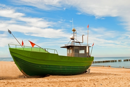 Green fishing boat on the Baltic seashore photo
