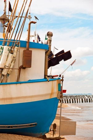 Blue fishing boat on the Baltic seashore photo