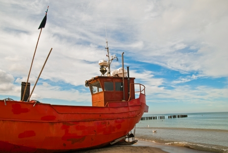 Red old rusty fishing boat on the Baltic seashore photo