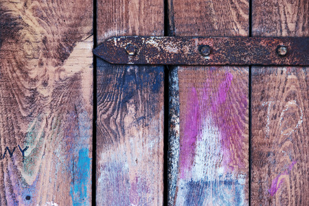 Vintage old wood colored door with rusted hinge photo