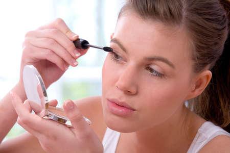 Young girl applying mascara on her eyelash photo