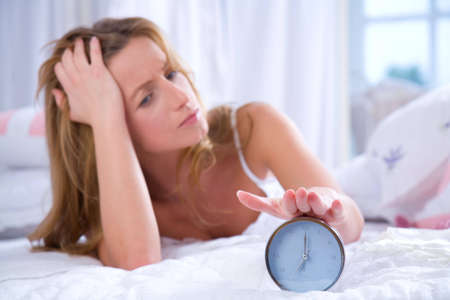 Young woman with her hand on an alarm clock Stock Photo - 5760899