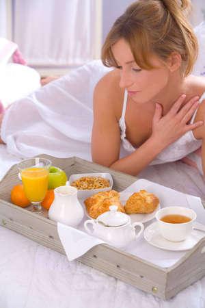 Beautiful woman having breakfast in bed photo