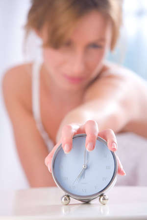 Young woman with her hand on an alarm clock Stock Photo - 5760897